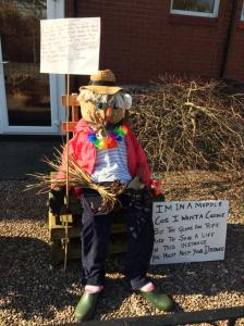 Charlie the scarecrow with a sign saying I'm in a muddle, cos I want a cuddle, but the germs are rife, and to save a life, in this instance you must keep your distance