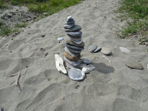 A cairn of rounded pebbles on a sandy path