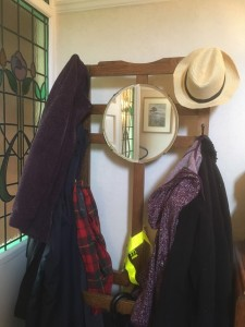 A view of coats and a sunhat on the hall stand with the circular mirror in the centre reflecting the door and stained glass window panel.
