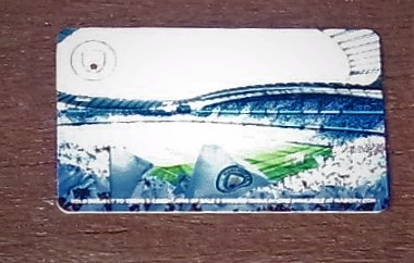 The back of Tony's Manchester City football club season card showing the crowded stadium and a sunlit pitch.