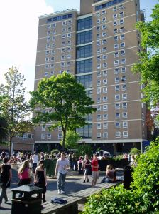 A photograph of the sixteen storey tower Joe lived in as a student, taken on a sunny day with lots of young people in the foreground.