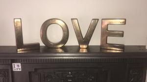 "Freestanding capital letters made from shiny metal spelling the word ""LOVE"""