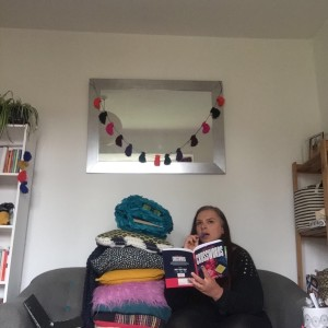 A photograph of Lucy with her cushion monster sitting on the sofa, with a crossword puzzle book.