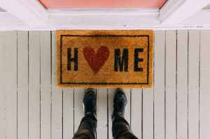 Looking down at a doormat in front of a closed door.  Home is written on the doormat with a heart instead of the letter O.  You can also see the bottom of a man's legs, wearing jeans and trainers, standing in front of the mat.