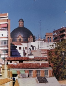 A view across rooftops to a domed, brick built church.