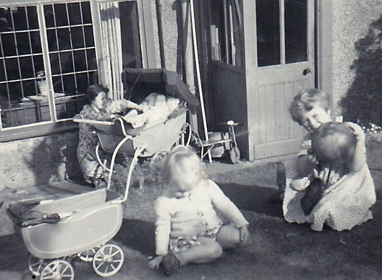 My mother with the large carriage pram and my baby sister, me next to our doll's pram and my older sister playing with a ball.