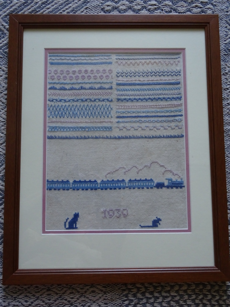 Lines of very neat stitching in different embroidery styles in pink and blue threads, beneath which is a stitched steam train in different shades of blue, with the steam in pink.  The date 1939 is in pink, with a cat to the left and a mouse to the right.