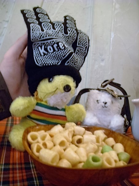 Gerard's lion wearing a baseball glove labelled Korea, seated next to a white stuffed toy bear in front of a bowl of Hula Hoops