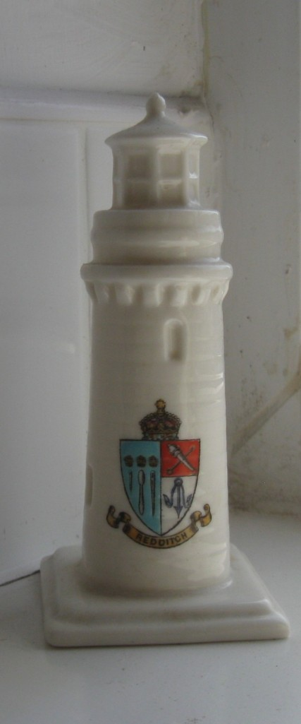 The white lighthouse is glazed china, showing two small arched windows and the lantern style light on the top. The crest is in blue and red, showing needles and other tools, with a gold crown on top and a furled ribbon bearing the name Redditch in capital letters.
