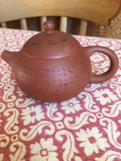 The terracotta teapot with Chinese writing on the lid and all round the  body