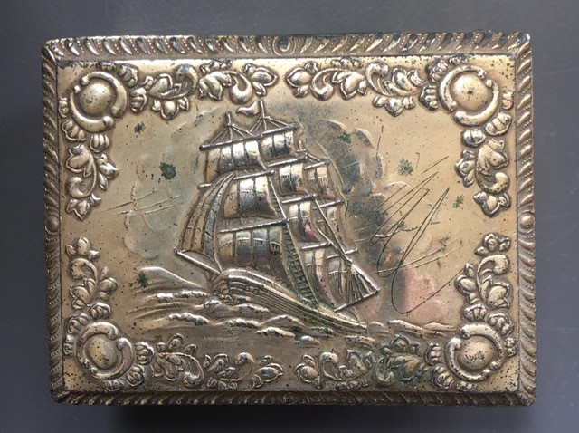 The lid of a metal jewellery box showing a ship sailing on the sea, with an ornate embossed border of leaves and flowers
