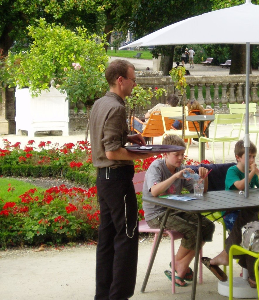 Joe is wearing a waiter's apron and holding a tray flat on his right hand, next to a table where a family are seated with drinks and a menu.  In the background are flowerbeds with red geraniums, a rose tree with pink roses and people seated or walking along the path through the park, beneath the trees.