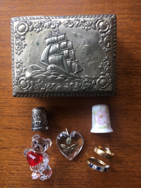 Linda's jewellery box and contents: the silver thimble, two rings, the perspex heart with the RAF symbol, the crystal teddy bear