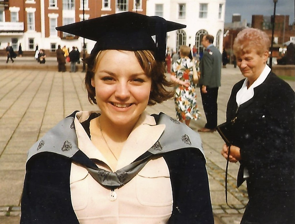 Jolene smiling radiantly in her graduation gown and mortarboard, with her Nan smiling proudly behind her.