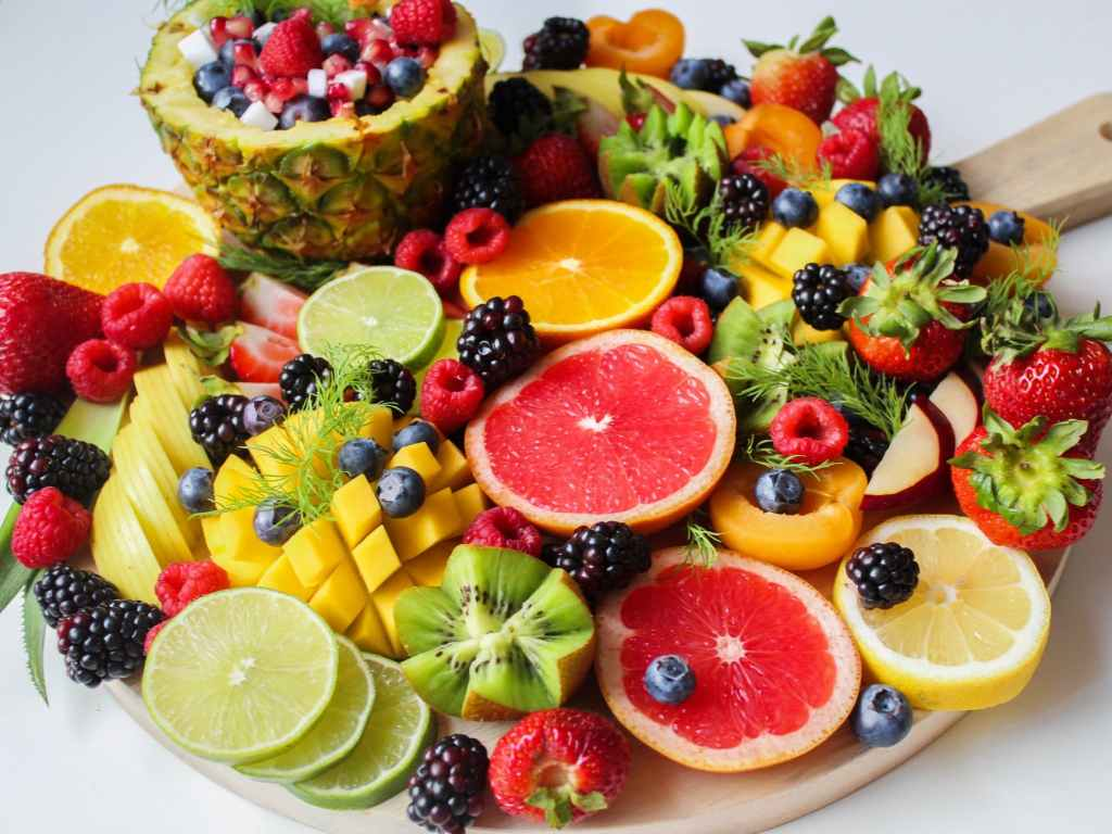 A platter of pineapples, limes, strawberries, kiwi fruit, blackberries, blueberries and apricots