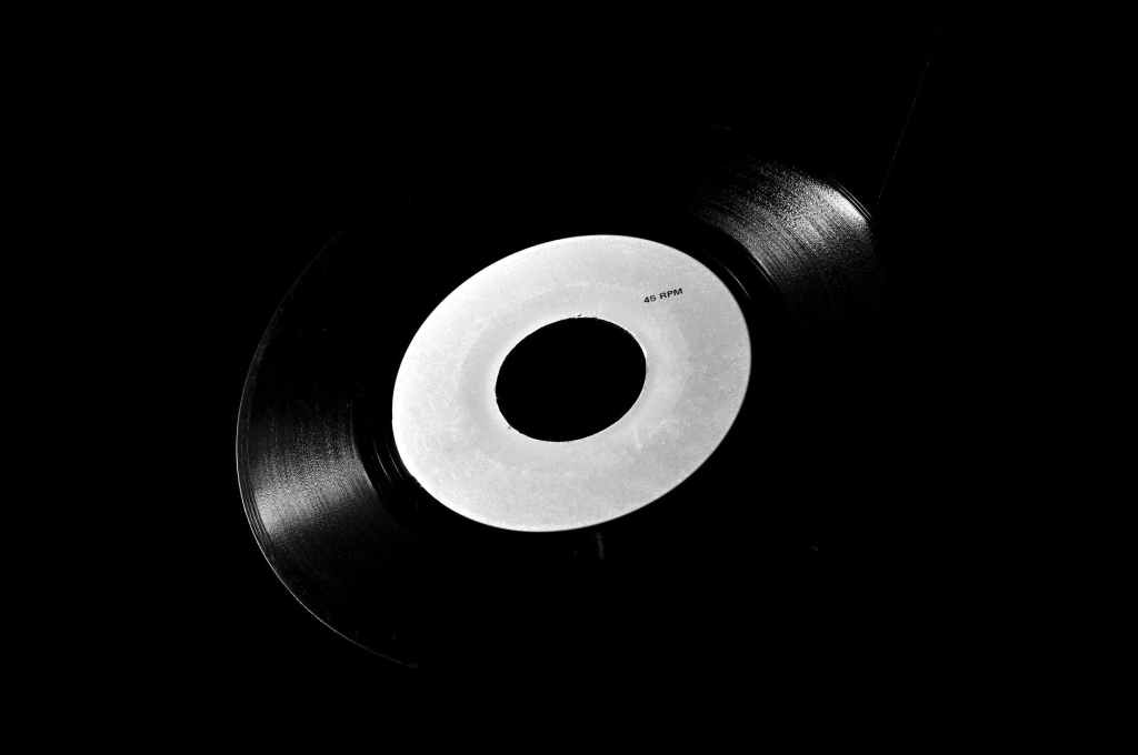 Black and white photograph of a vinyl 45 RPM record, one track on each side