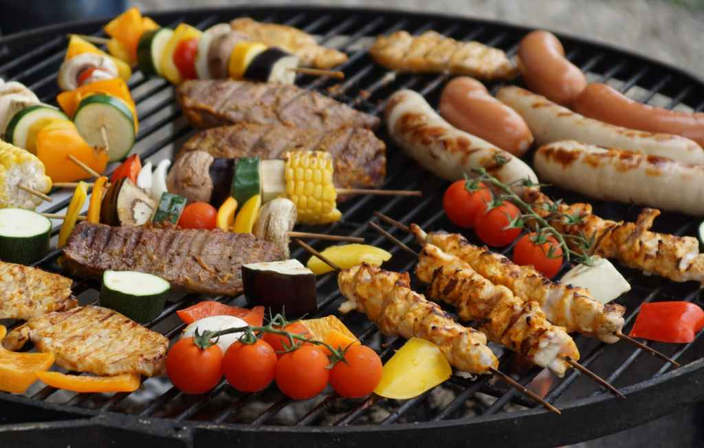 sausages, beefburgers, vegetable skewers and tomatoes cooking on a barbecue