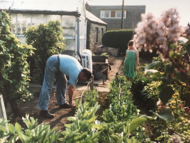 Linda's Uncle is bending over to tend to a row of tomatoes in front of his greenhouse.  Linda's daughter is watching with interest