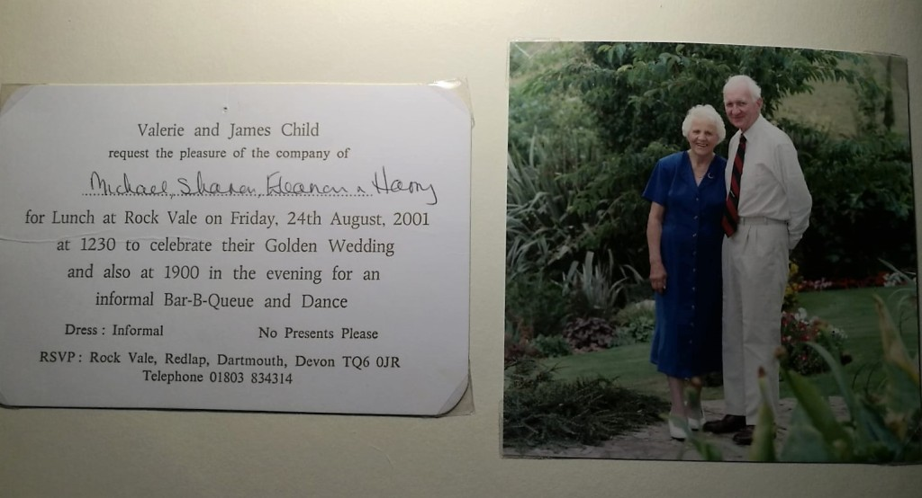 Page from a photograph album showing the invitation for lunch at 12.30 and barbecue and dance at 19.00 to celebrate the Golden Wedding of Valerie and James Child on 24th August 2001.  To the right of the invitation is a photograph of the couple in a beautiful formal garden.