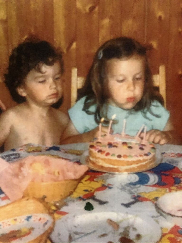 Lucy in a summer dress, blowing out five candles on her pink birthday cake decorated with Smarties., with her brother next to her