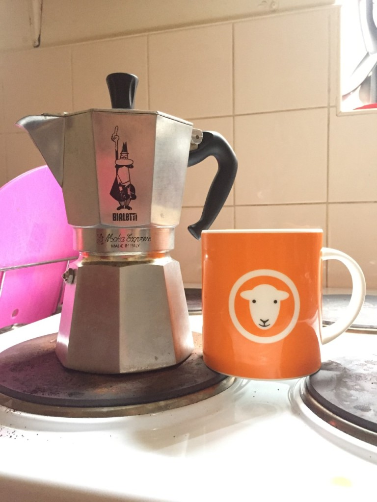 An Italian Moka Espresso coffee pot, with a black handle and a cartoon  image of a man making the thumbs up sign.  Next to it on the draining board is a bright orange mug with a white handle.