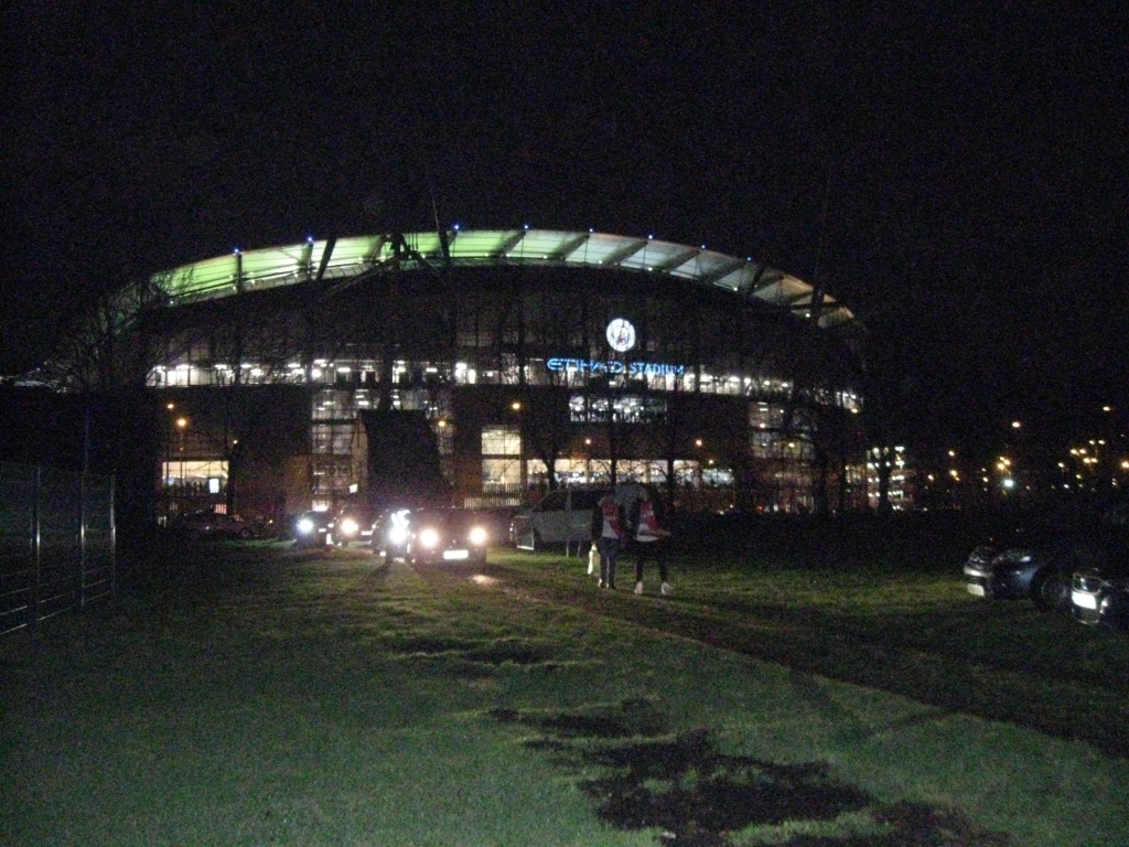 Tony's photograph of the flood lit stadium with the headlights of cars leaving and two people walking along the pavement