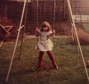 Lucy, aged 5, seated on her swing on the lawn in her garden.