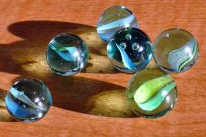 Six glass marbles on a wooden floor