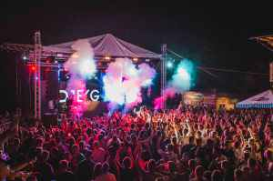 A festival music stage at night time, with crowds of people waving their hands in the air