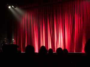 Spotlight shining onto drawn stage curtains with silhouettes of audience members