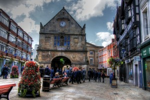 The square in the centre of Shrewsbury, showing the old market hall, benches, floral displays and people walking by
