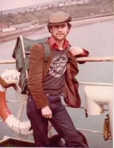 Young Tony on board a ferry, wearing a flat cap, a Guinness jumper over a red shirt with a large collar and a brown corduroy jacket. He is carrying a large framed rucksack on his back.