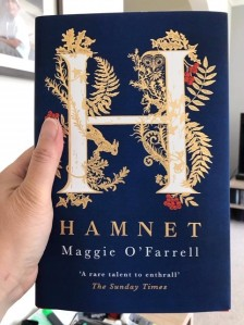 Linda's hand holding Hamnet, by Maggie O'Farrell.  The dark blue cover has an illuminated H with gold foliage, red berries, a gold owl at the top right and a gold rabbit running downwards on the bottom left