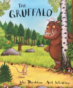 The cover of The Gruffalo written by by Julia Donaldson and illustrated by Axel Sheffler.  It shows the large smiling Gruffalo in the woods and a little mouse walking along a path.