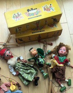 Four puppets laid out on the floor with their strings, with the distinctive yellow boxes behind them