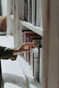A woman's hand choosing books from a tightly packed bookshelf