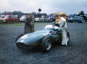 Stirliing Moss and colleagues beside his 1950s racing car, with other cars of those times parked in a car park behind.