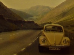 The yellow Beetle, parked on the side of the road with a view of mountains and a lake behind