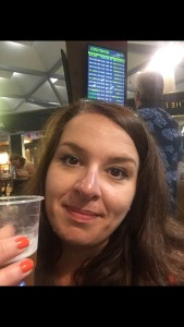 A selfie of Lucy in the airport with a glass of beer
