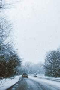 snowy road seen through a car windscreen