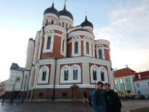 Ellie and her partner standing in front of a pink and white Russian Orthodox style church in a square in Talinn