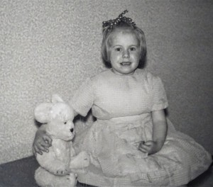 A photograph of Margaret as a child with a ribbon in her hair, wearing a party dress with her arm round her seated teddy bear