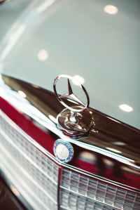 Close up of a Mercedes logo on a car bonnet
