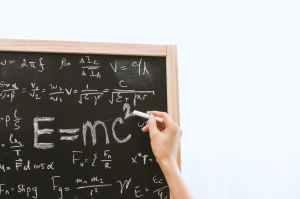 A school chalk board full of Physics formulas, with the teacher's hand holding chalk finishing Einstein's formula E=mc
