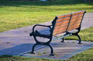 A wrought iron park bench with a wooden seat, next to a path alongside a mowed lawn