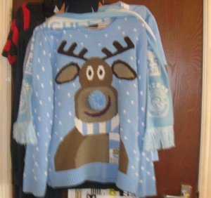 A Christmas jumper in the colours of the Manchester City football kit (light blue and white) on which is a brown reindeer with a blue pompom for a nose and wearing a Manchester City football scarf .