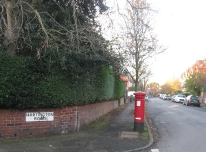 The red post box at the junction of Hartington Road and Corkland Road, Chorlton, with the sun shining on the Autumnal trees