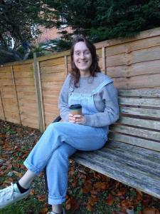 A photograph of Ellie sitting on a bench besides a garden fence with a takeaway cup of coffee.  She is smiling at the camera.  She is wearing blue dungarees over a grey jumper and trainers.  There are autumn leaves on the grass around her.