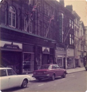 A street view of David Morgan's store in Cardiff. There are furled Union Jacks on flag posts outside the shop front and an entrance to the Morgan Arcade.  There are cars from the 1970s parked outside.