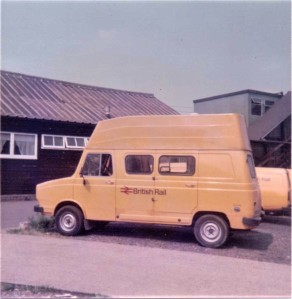 A yellow British Rail van in a car park outside a single story wooden building, with open windows and a corrugated roof.